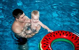 Father and son are swimming in the pool stock photo