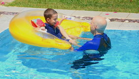 Father and son in a swimming pool. Father and son having fun in the swimming pool with a floating cushion / seat Royalty Free Stock Image