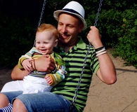 Father and son on a swing. Father and his baby son on a swing Royalty Free Stock Photography