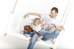 Father and son on a swing with ukulele guitar Stock Image