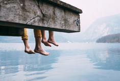 Father and son swung their legs from the wooden pier on mountain. Lake Stock Photos