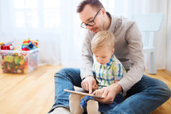 Father and son with tablet pc playing at home Royalty Free Stock Images