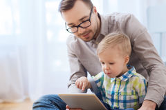 Father and son with tablet pc playing at home Royalty Free Stock Photography
