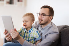 Father and son with tablet pc playing at home Stock Images
