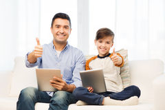 Father and son with tablet pc showing thumbs up Royalty Free Stock Photos