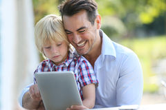 Father and son on tablet smiling Stock Photos