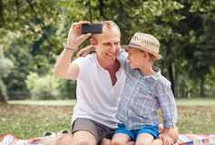 Father and son take a self picture with a phone Royalty Free Stock Image