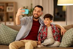 Father and son taking selfie at home. People, family and technology concept - happy father and little son taking selfie by smartphone sitting on sofa at home in stock photography
