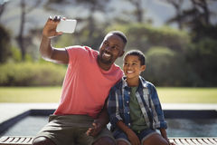 Father and son taking selfie with mobile phone Royalty Free Stock Images
