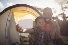 Father and son taking selfie with mobile phone in park Royalty Free Stock Photography