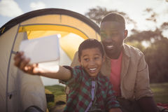 Father and son taking selfie with mobile phone in park Royalty Free Stock Images