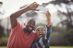 Father and son taking selfie with mobile phone Royalty Free Stock Photos