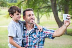 Father and son taking a selfie in the park Royalty Free Stock Photos