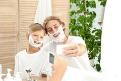 Father and son taking selfie with shaving foam on faces. In bathroom stock image