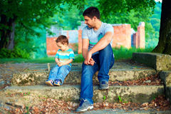 Father and son talk, while sitting on old stairs among trees Stock Image