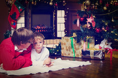 Father and son talking by a fireplace on Christmas Stock Photo