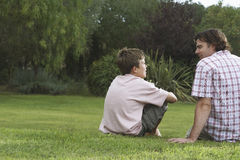 Father And Son Talking In Lawn. Rear view of father and son sitting on lawn and talking Stock Image