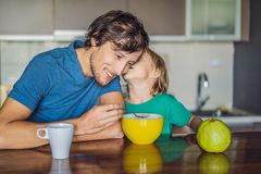 Father and son are talking and smiling while having a breakfast in kitchen royalty free stock image