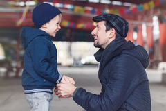 Father and son talking to each other holding hands looking at each other. Portrait of smiling laughing white Caucasian father and son talking to each other Stock Photography