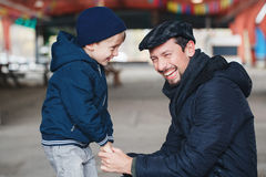 Father and son talking to each other holding hands looking at each other. Portrait of smiling laughing white Caucasian father and son talking to each other Royalty Free Stock Photo