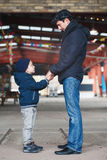 Father and son talking to each other holding hands looking at each other. Portrait of white Caucasian father and son talking to each other holding hands looking Stock Photos