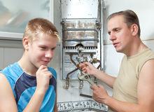 Father and son-teenager together in repair heater Royalty Free Stock Photo