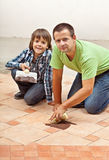 Father and son testing the joint material color on ceramic tiles Stock Photography