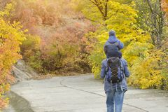 Father and son on their shoulders walk through the autumn park. Back view royalty free stock photos
