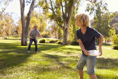 Father And Son Throwing Frisbee In Park Together Royalty Free Stock Photos
