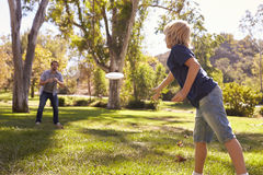 Father And Son Throwing Frisbee In Park Together Stock Photography