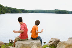 Father and son throwing rocks into lake Royalty Free Stock Photography