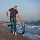 Father and son to the sea at sunset Stock Photo