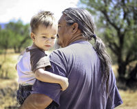 Father and son. Father and toddler son from the Pascua Yaqui tribe of Arizona. Man with long hair and ponytail holding his young son outdoors in nature Royalty Free Stock Photo