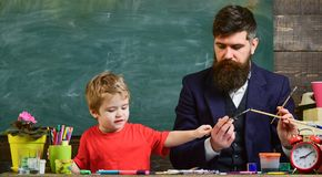 Father and son together in the art center. Dad holding paintbrushes while kid is choosing colors. Private education. Concept royalty free stock photos