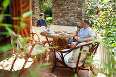 Father and son together on patio Royalty Free Stock Image