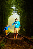 Father and son together in railway green tunnel Royalty Free Stock Photography