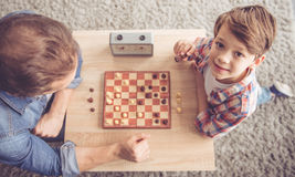Father and son. Top view of father and son playing chess while spending time together at home. Little boy is looking at camera and smiling Stock Photos