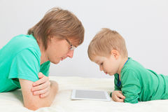 Father and son with touch pad at home Stock Images
