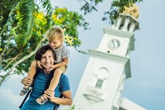 Father and son of tourists in the background of Queen Victoria Memorial clock tower, Penang.  royalty free stock photography