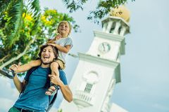 Father and son of tourists in the background of Queen Victoria Memorial clock tower, Penang.  royalty free stock images