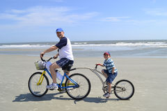 Father and son on alley cat bike at the beach. Father and young boy standing with rental alley cat bikes on the beach Royalty Free Stock Photos
