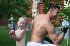 Father and son train with dumbbells Royalty Free Stock Photo