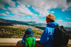 Father and son travel in nature, looking at mountains royalty free stock photography