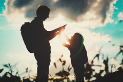 Father and son travel in sunset nature. Silhouette of father and son travel in sunset nature stock photography