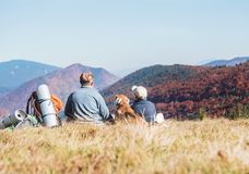 Father and son travelers with their beagle dog sit together in m. Ountain valley with beautiful hills view royalty free stock photos