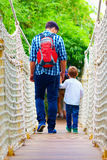 Father and son travelling by suspension bridge Royalty Free Stock Photo