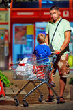 Father and son with trolley after shopping. Father and son with trolley after evening shopping Royalty Free Stock Photos