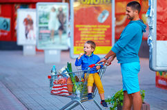 Father and son with trolley after shopping. Father and son with trolley after evening shopping Stock Photos