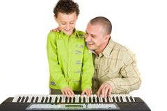 Father and son trying to play piano. Father and son having fun trying to play piano Royalty Free Stock Image