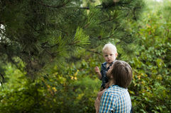 Father and son under a pine branch Royalty Free Stock Photo